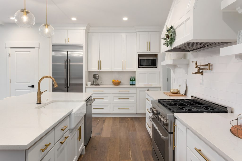 A spacious kitchen with white cabinet doors and gold hardware