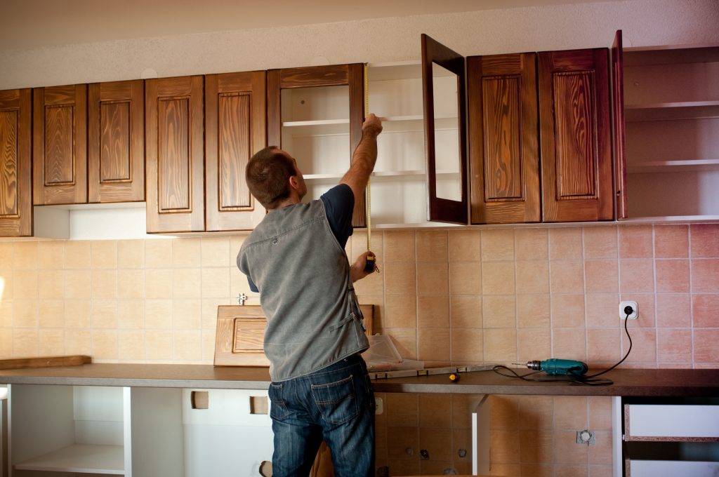 A man installing new cabinets
