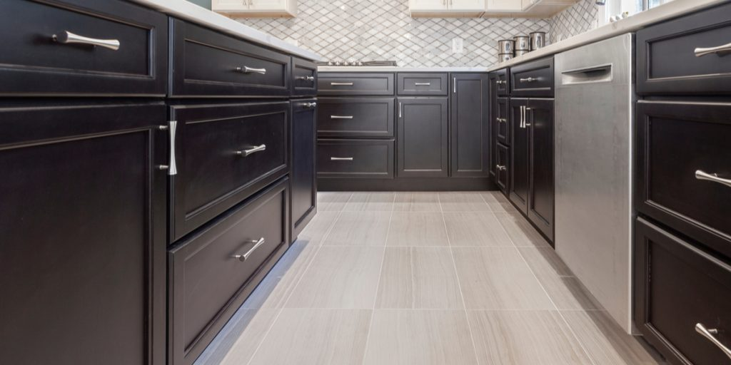 A kitchen with dark lower cabinets and new shaker doors